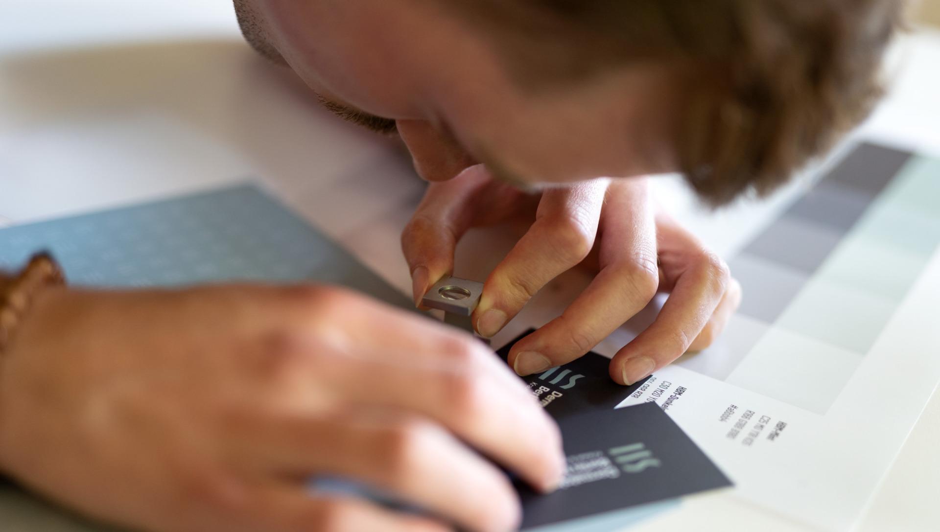 Mann prüft mit Fadenzähler Visitenkarten