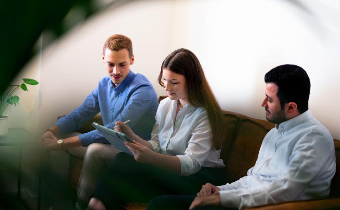 Drei Personen mit iPad in der Hand auf der Couch