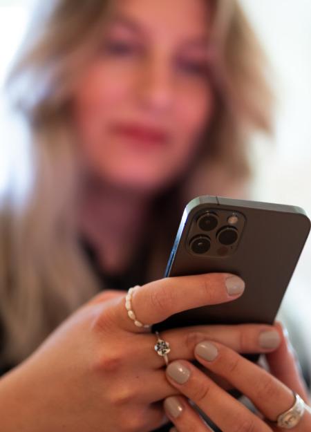 Frau hält iPhone in Hand