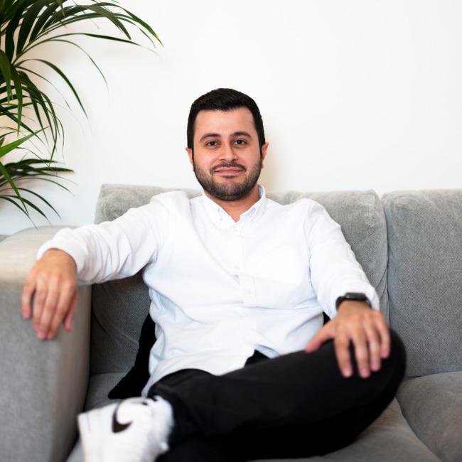 Ibrahim grinsend auf grauer Couch