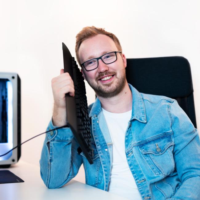 Marin sitzt auf Bürostuhl und telefoniert mit Tastatur