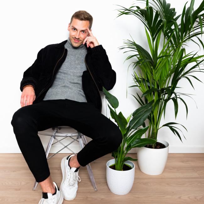 Nils sitzt auf einem Stuhl neben Pflanzen